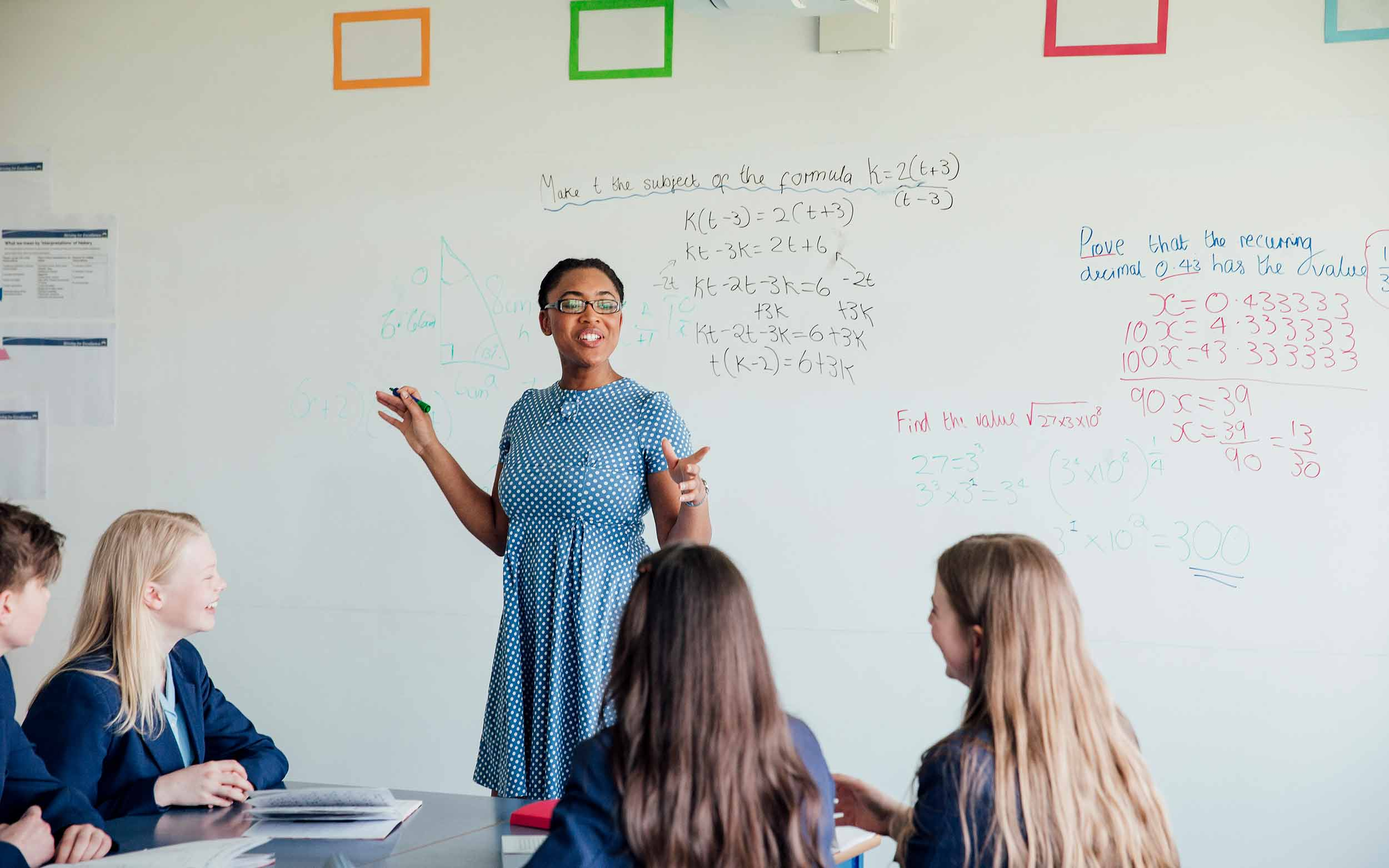 Female teacher in front of whiteboard and class